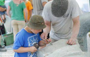 Kind arbeitet mit an der Natursteinskulptur