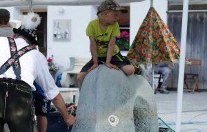Kind auf Seeschlange aus Stein